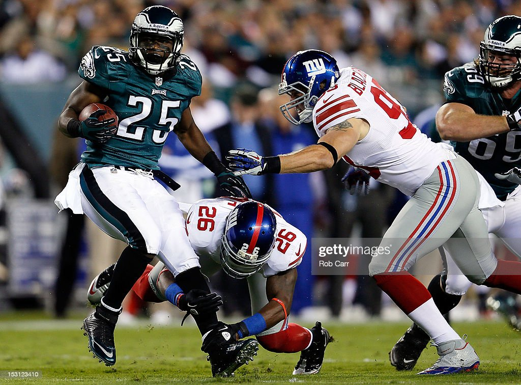 Running back LeSean McCoy of the Philadelphia Eagles is tackled by free safety Antrel Rolle and middle linebacker Chase Blackburn of the New York...