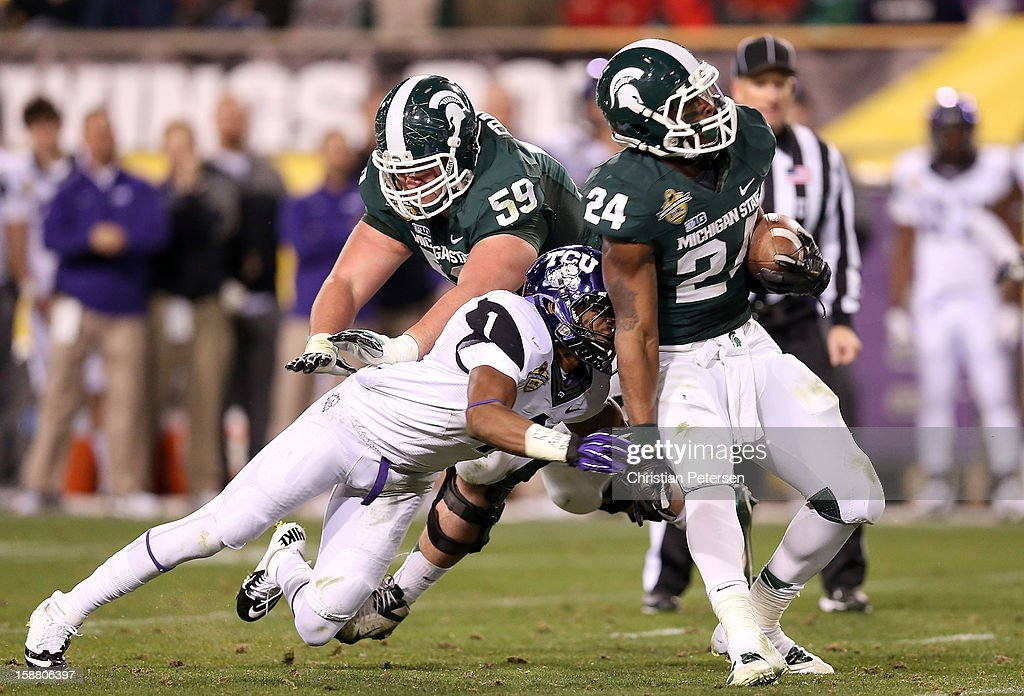Running back Le'Veon Bell #24 of the Michigan State Spartans is tackled by safety Chris Hackett #1 of the TCU Horned Frogs during the Buffalo Wild Wings Bowl at Sun Devil Stadium on December 29, 2012 in Tempe, Arizona. The Spartans defeated the Horned Frogs 17-16.