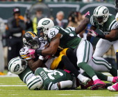 Running back Le'Veon Bell of the Pittsburgh Steelers is gang tackled by linebacker David Harris safety Antonio Allen and linebacker Calvin Pace of...