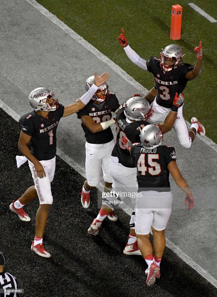 Running back Lexington Thomas #3 of the UNLV Rebels celebrates in the end zone with teammates including quarterback Armani Rogers (L) #1 after scoring on a three-yard run against the Howard Bison during their game at Sam Boyd Stadium on September 2, 2017 in Las Vegas, Nevada. Howard won 43-40.