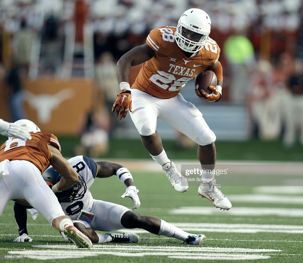 Running back Malcolm Brown of the Texas Longhorns goes airborne to avoid West Virginia Mountaineer defenders in the NCAA Big 12 game between the...