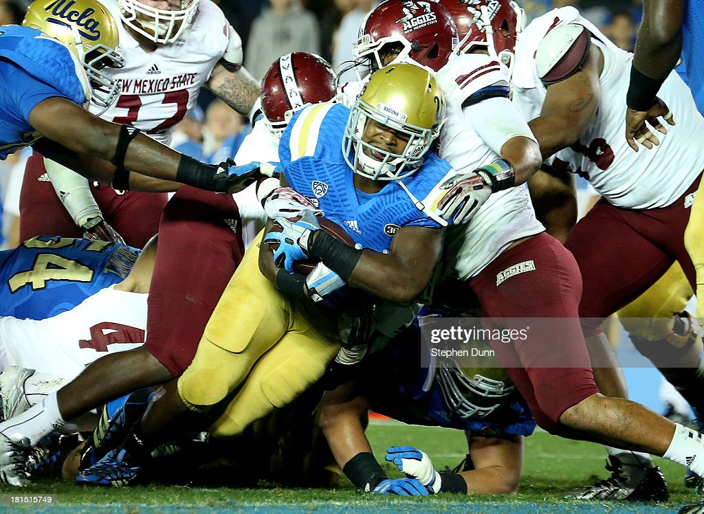 Running back Malcolm Jones #28 of the UCLA Bruins dives across the goal line for a three yard touchdown run in the fourth quarter against the New Mexico State Aggies at the Rose Bowl on September 21, 2013 in Pasadena, California. UCLA won 59-13.