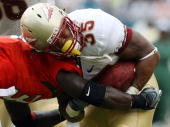 Running back Marcus Sims of the Florida State Seminoles is hit hard by defensive back Lovon Ponder of the Miami Hurricanes at Dolphin Stadium on...