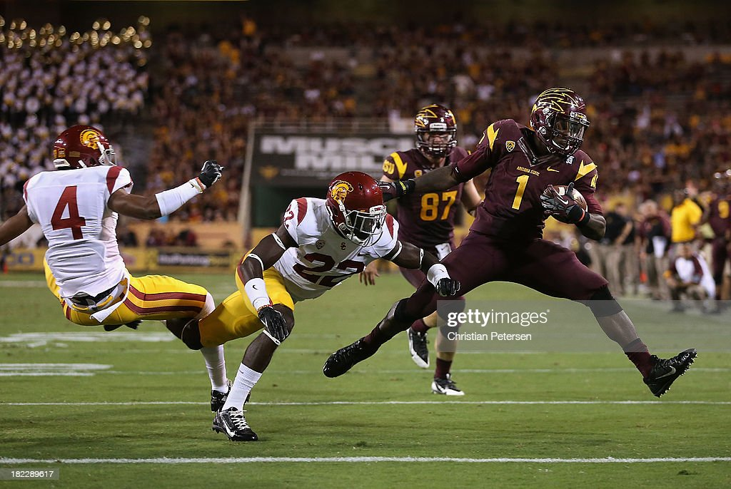 Running back Marion Grice #1 of the Arizona State Sun Devils rushes the football past cornerback Torin Harris #4 and safety Leon McQuay III #22 of the USC Trojans to score on a 8 yard rushing touchdown during the third quarter of the college football game at Sun Devil Stadium on September 28, 2013 in Tempe, Arizona.