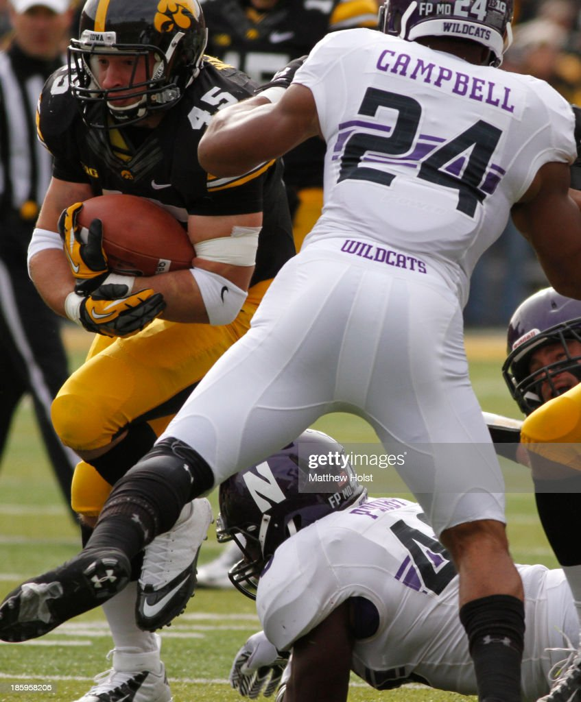 Running back Mark Weisman #45 of the Iowa Hawkeyes rushes up field during the first quarter past safety Ibraheim Campbell #24 and and linebacker Damien Proby #46 of the Northwestern Wildcats on October 26, 2013 at Kinnick Stadium in Iowa City, Iowa.