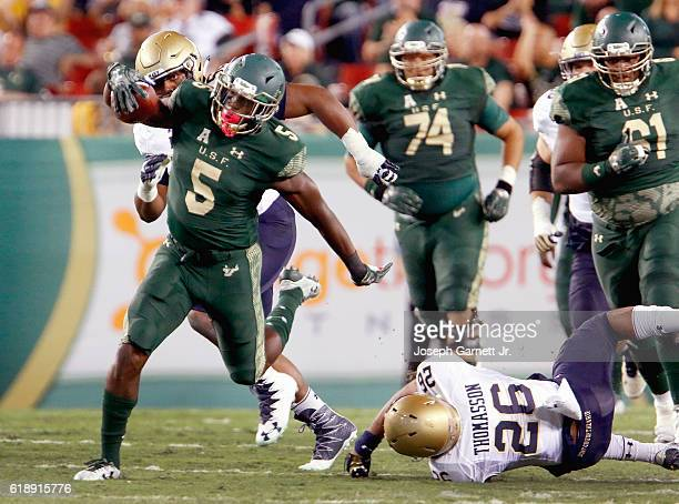 Running back Marlon Mack of the South Florida Bulls breaks through Navy defenders enroute to an 85yard touchdown run at Raymond James Stadium on...