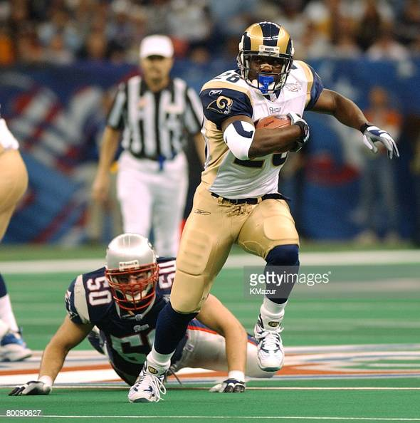 Running back Marshall Faulk of the St Louis Rams runs for a short gain under pressure by the New England Patriots during Super Bowl XXXVI at the...