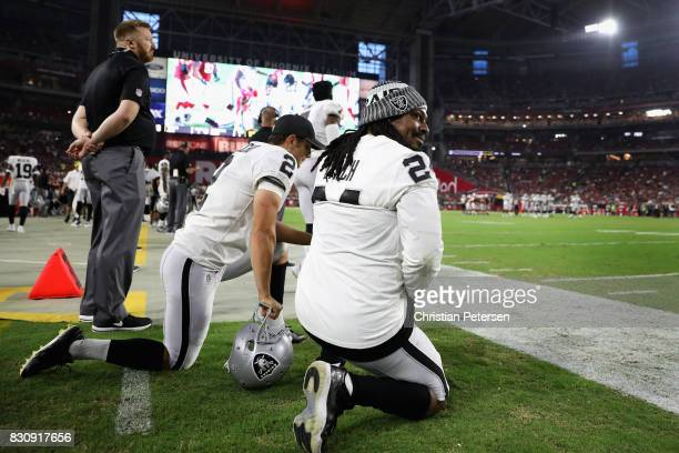 Running back Marshawn Lynch and kicker Giorgio Tavecchio of the Oakland Raiders kneel on the sidelines during the first half of the NFL game against...