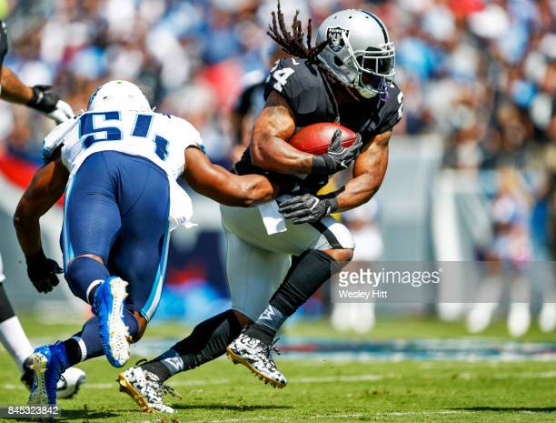 Running back Marshawn Lynch of the Oakland Raiders runs the ball past linebacker Avery Williamson of the Tennessee Titans in the first half at Nissan...