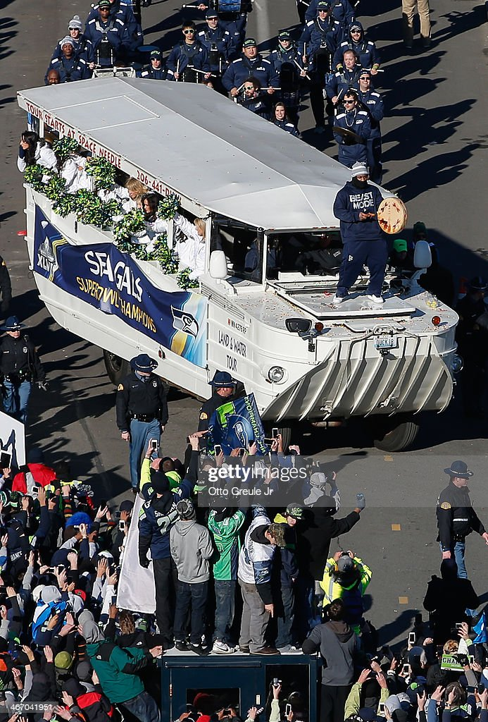 Running back Marshawn Lynch (standing on hood of vehicle) of the Seattle Seahawks beats a drum during the Seahawks' Super Bowl XLVIII Victory Parade on February 5, 2014 in Seattle, Washington.