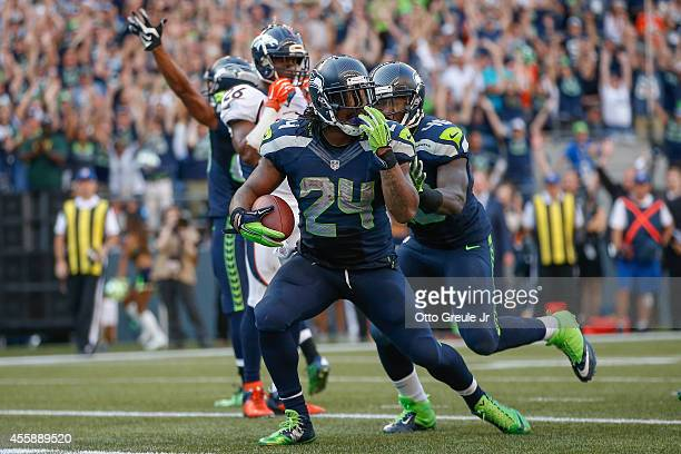 Running back Marshawn Lynch of the Seattle Seahawks celebrates after rushing for the winning touchdown in overtime against the Denver Broncos at...
