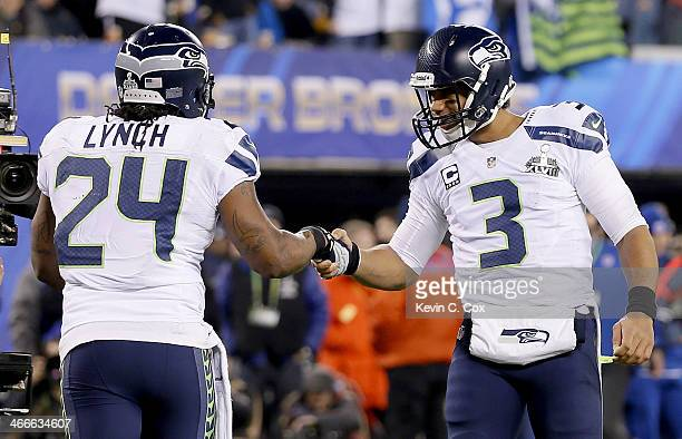 Running back Marshawn Lynch of the Seattle Seahawks celebrates his 1yard touchdown with teammate quarterback Russell Wilson in the second quarter...