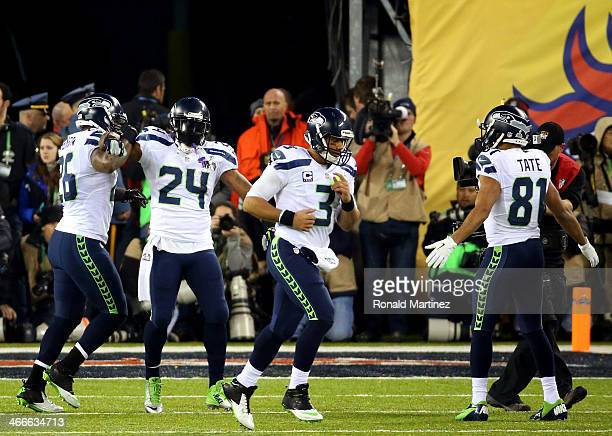 Running back Marshawn Lynch of the Seattle Seahawks celebrates his 1yard touchdown with teammate fullback Michael Robinson quarterback Russell Wilson...