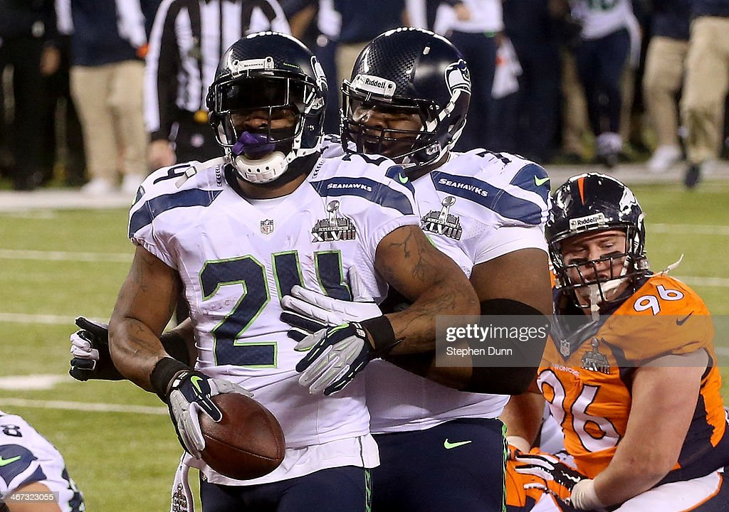 Running back <a gi-track='captionPersonalityLinkClicked' href=/galleries/search?phrase=Marshawn+Lynch&family=editorial&specificpeople=2159904 ng-click='$event.stopPropagation()'>Marshawn Lynch</a> #24 of the Seattle Seahawks celebrates his 1-yard touchdown with teammate tackle <a gi-track='captionPersonalityLinkClicked' href=/galleries/search?phrase=Alvin+Bailey&family=editorial&specificpeople=4596773 ng-click='$event.stopPropagation()'>Alvin Bailey</a> #78 in the second quarter against the Denver Broncos during Super Bowl XLVIII at MetLife Stadium on February 2, 2014 in East Rutherford, New Jersey.