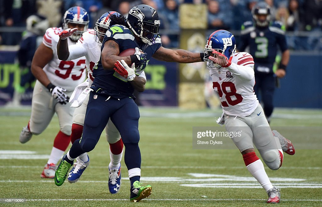 Running back Marshawn Lynch of the Seattle Seahawks gives cornerback Jayron Hosley of the New York Giants a stiff arm during the first quarter of the...