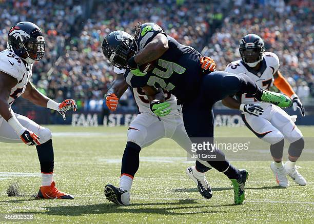 Running back Marshawn Lynch of the Seattle Seahawks goes airborne while being tackled by middle linebacker Nate Irving of the Denver Broncos at...