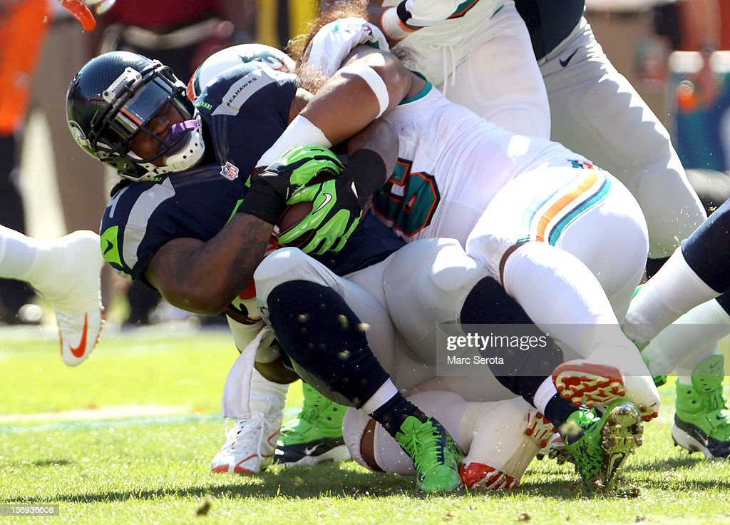 Running back Marshawn Lynch #24 of the Seattle Seahawks is brought down against the Miami Dolphins at Sun Life Stadium on November 25, 2012 in Miami Gardens, Florida.