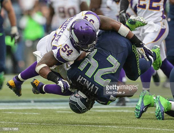 Running back Marshawn Lynch of the Seattle Seahawks is tackled by middle linebacker Jasper Brinkley of the Minnesota Vikings at CenturyLink Field on...