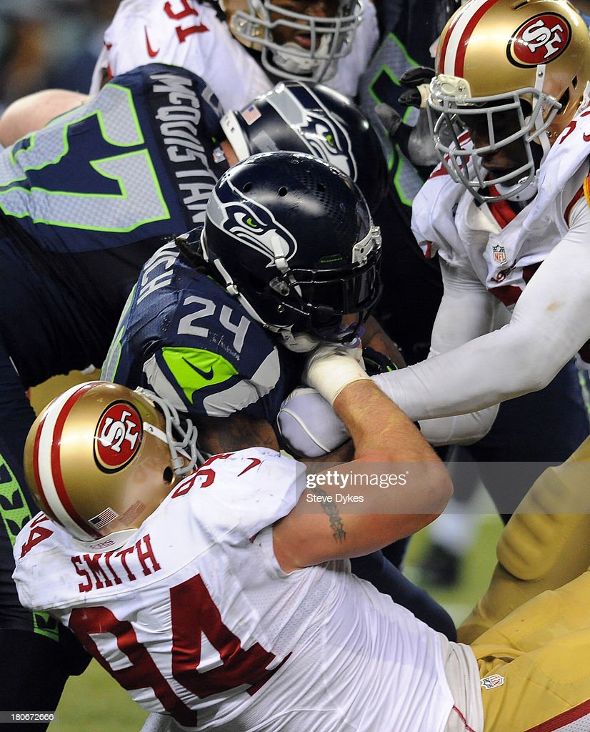 Running back Marshawn Lynch #24 of the Seattle Seahawks is tackled by outside linebacker Aldon Smith #99 of the San Francisco 49ers and defensive end Justin Smith #94 of the San Francisco 49ers during the first quarter of the game at CenturyLink Field on September 15, 2013 in Seattle, Washington.