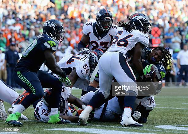 Running back Marshawn Lynch of the Seattle Seahawks loses his helmet while being tackled by middle linebacker Nate Irving of the Denver Broncos at...