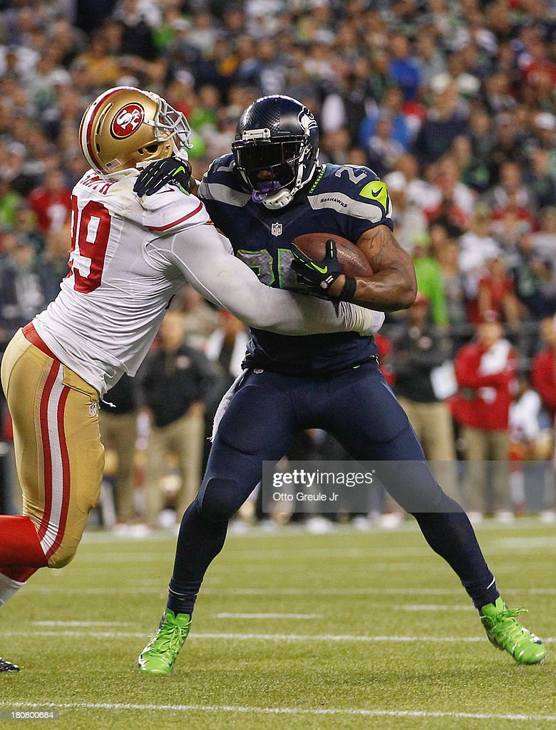 Running back Marshawn Lynch #24 of the Seattle Seahawks rushes against linebacker Aldon Smith #99 of the San Francisco 49ers at CenturyLink Field on September 15, 2013 in Seattle, Washington.