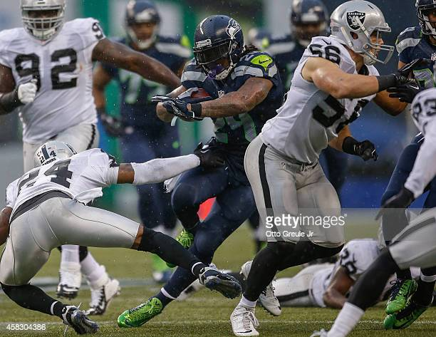 Running back Marshawn Lynch of the Seattle Seahawks rushes against the Oakland Raiders at CenturyLink Field on November 2 2014 in Seattle Washington...