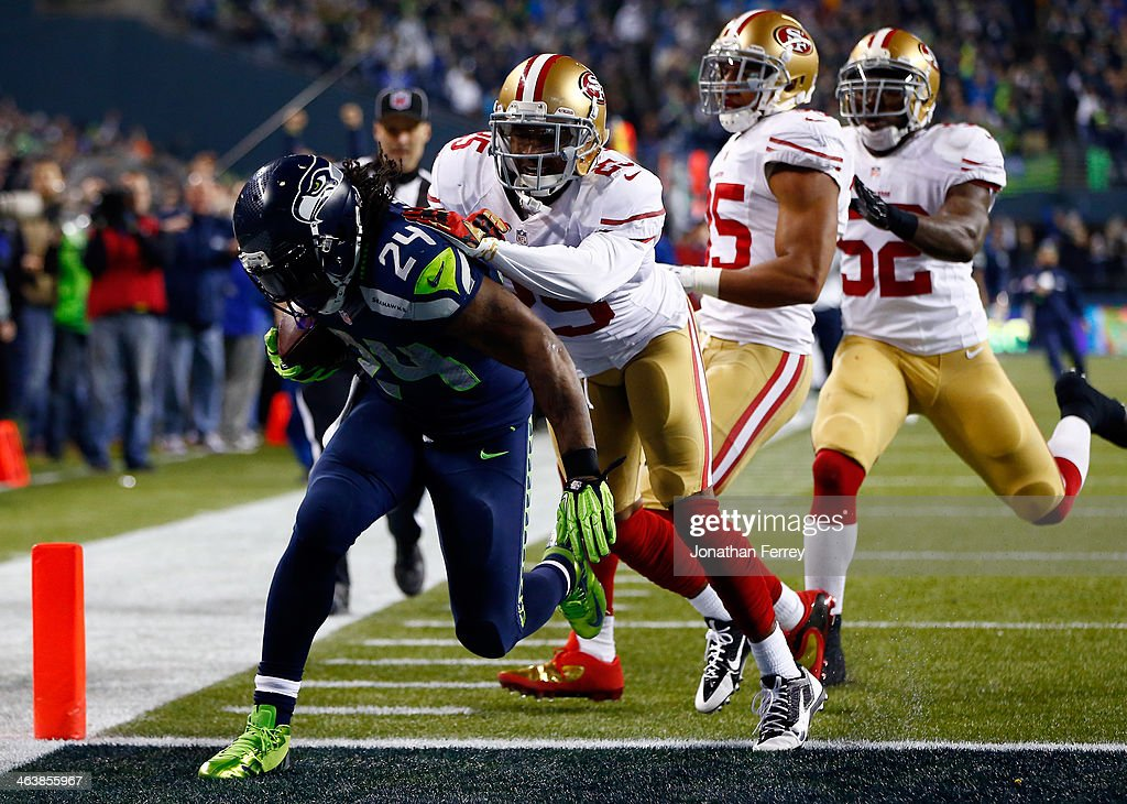 Running back <a gi-track='captionPersonalityLinkClicked' href=/galleries/search?phrase=Marshawn+Lynch&family=editorial&specificpeople=2159904 ng-click='$event.stopPropagation()'>Marshawn Lynch</a> #24 of the Seattle Seahawks scores a 40-yard touchdown against cornerback <a gi-track='captionPersonalityLinkClicked' href=/galleries/search?phrase=Tarell+Brown&family=editorial&specificpeople=2105844 ng-click='$event.stopPropagation()'>Tarell Brown</a> #25 of the San Francisco 49ers in the third quarter during the 2014 NFC Championship at CenturyLink Field on January 19, 2014 in Seattle, Washington.