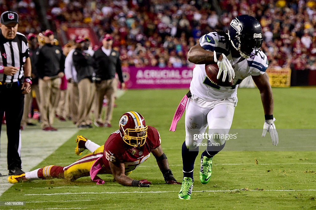 Running back Marshawn Lynch of the Seattle Seahawks scores a 4th quarter touchdown past the defense of inside linebacker Perry Riley of the...
