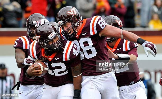 Running back Marshawn Williams of the Virginia Tech Hokies celebrates his touchdown run with teammate tight end Ryan Malleck against the Boston...