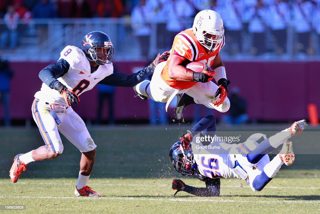 Running back Martin Scales #25 of the Virginia Tech Hokies leaps while running with the ball to avoid safety Anthony Harris #8 of the Virginia Cavaliers and cornerback Maurice Canady #26 of the Cavaliers at Lane Stadium on November 24, 2012 in Blacksburg, Virginia.