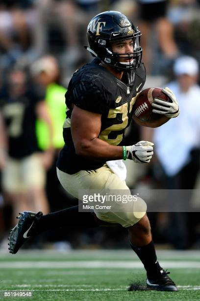 Running back Matt Colburn of the Wake Forest Demon Deacons runs the ball against the Utah State Aggies during the football game at BBT Field on...