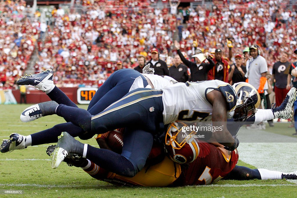 Running back Matt Jones of the Washington Redskins scores a fourth quarter touchdown past defensive end Robert Quinn of the St Louis Rams and outside...
