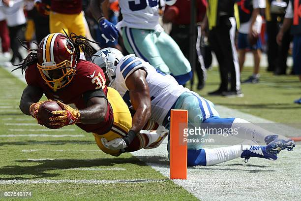 Running back Matt Jones of the Washington Redskins scores a second quarter touchdown past strong safety Barry Church of the Dallas Cowboys at...