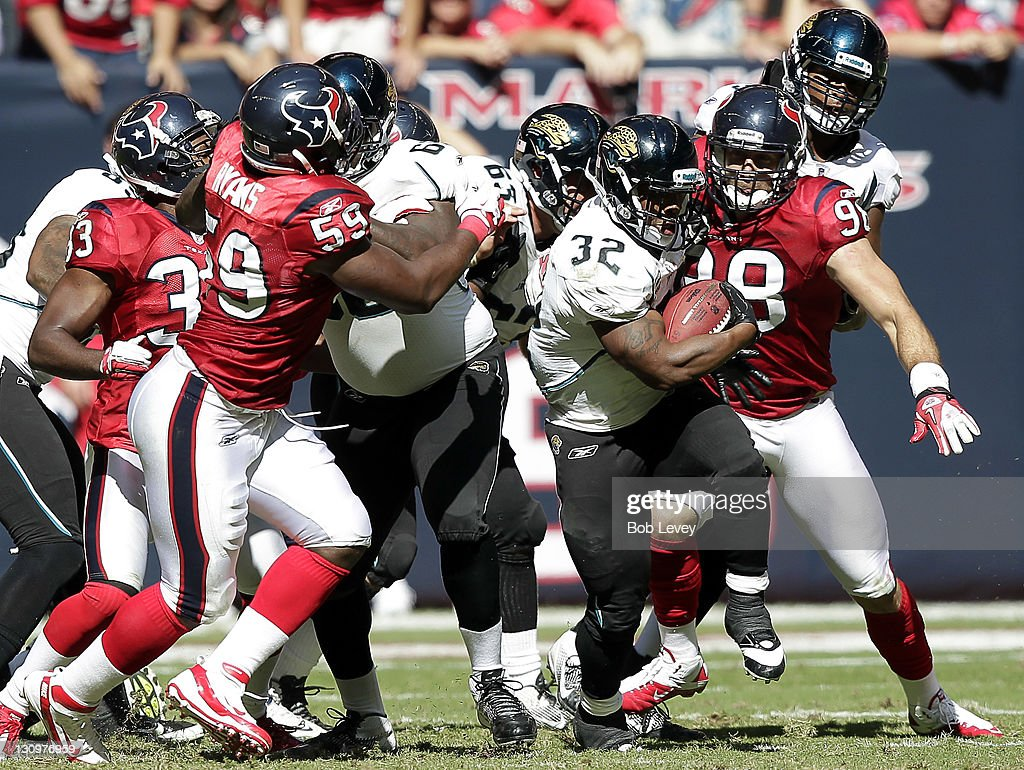 Running back Maurice Drew-Jones #32 of the Jacksonville Jaguars breaks through a hole of the Houston Texans defense as linebacker DeMeco Ryans #59 and <a gi-track='captionPersonalityLinkClicked' href=/galleries/search?phrase=J.J.+Watt&family=editorial&specificpeople=6243554 ng-click='$event.stopPropagation()'>J.J. Watt</a> #99 at Reliant Stadium on October 30, 2011 in Houston, Texas.