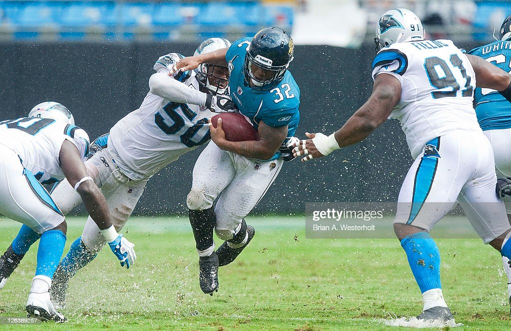 Running back <a gi-track='captionPersonalityLinkClicked' href=/galleries/search?phrase=Maurice+Jones-Drew&family=editorial&specificpeople=243147 ng-click='$event.stopPropagation()'>Maurice Jones-Drew</a> #32 of the Jacksonville Jaguars gets hit by linebacker James Anderson #50 of the Carolina Panthers during third quarter action at Bank of America Stadium on September 25, 2011 in Charlotte, North Carolina. The Panthers defeated the Jaguars 16-10.