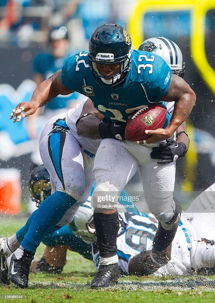 Running back <a gi-track='captionPersonalityLinkClicked' href=/galleries/search?phrase=Maurice+Jones-Drew&family=editorial&specificpeople=243147 ng-click='$event.stopPropagation()'>Maurice Jones-Drew</a> #32 of the Jacksonville Jaguars tries to escape the grasp of a Carolina Panthers defender during third quarter action at Bank of America Stadium on September 25, 2011 in Charlotte, North Carolina. The Panthers defeated the Jaguars 16-10.