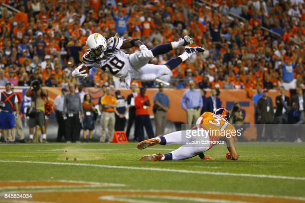 Running back Melvin Gordon of the Los Angeles Chargers dives over strong safety Justin Simmons of the Denver Broncos in the second quarter at Sports...