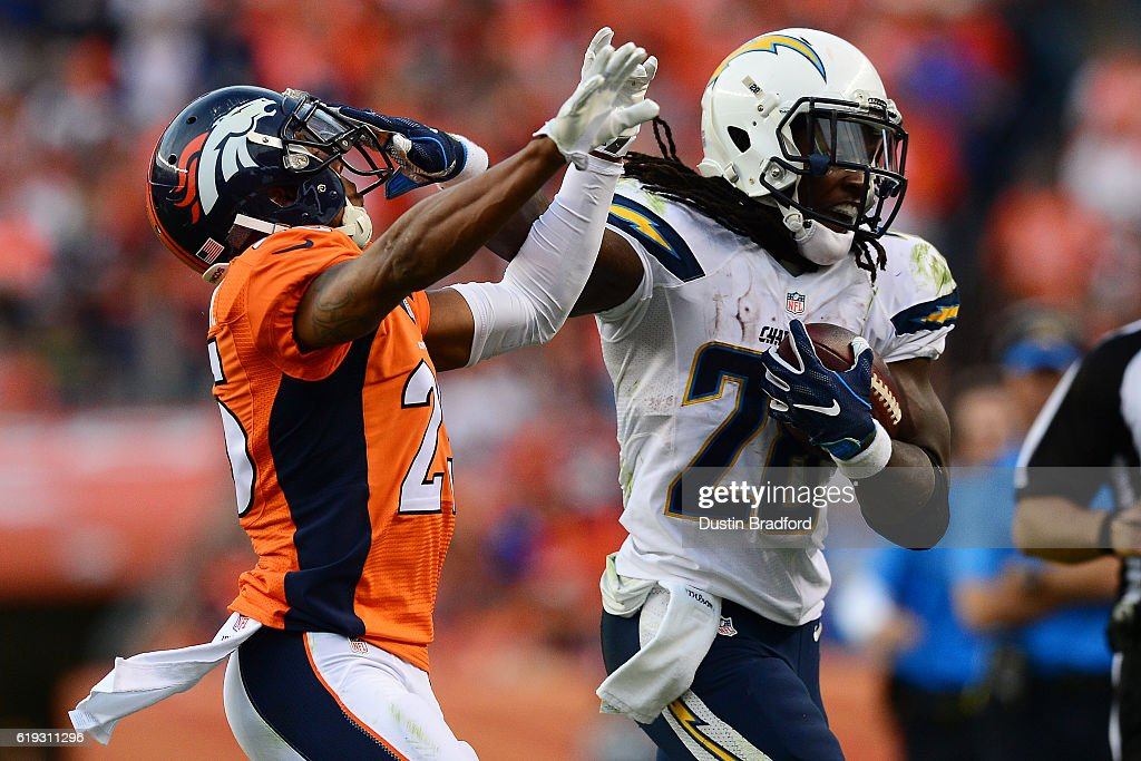 Running back Melvin Gordon #28 of the San Diego Chargers fights off cornerback Chris Harris #25 of the Denver Broncos in the fourth quarter of the game at Sports Authority Field at Mile High on October 30, 2016 in Denver, Colorado.