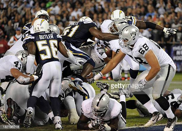 Running back Michael Bush of the Oakland Raiders dives over the pile to score a twoyard touchdown in the first half against the San Diego Chargers at...