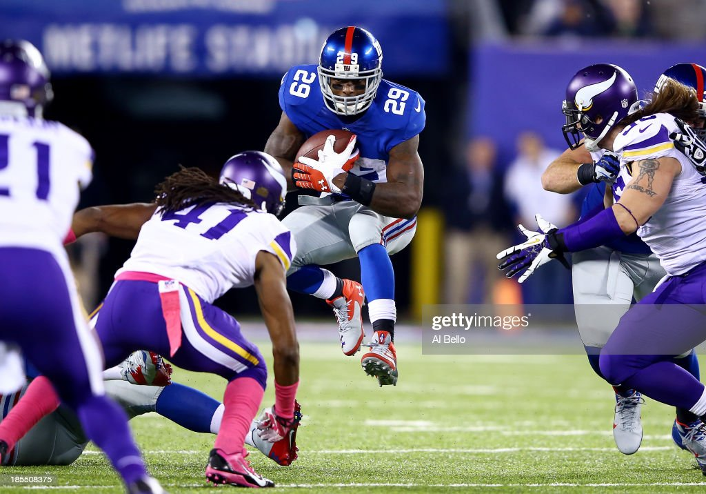 Running back Michael Cox #29 of the New York Giants runs with the ball as strong safety Mistral Raymond #41 of the Minnesota Vikings defends during a game at MetLife Stadium on October 21, 2013 in East Rutherford, New Jersey.