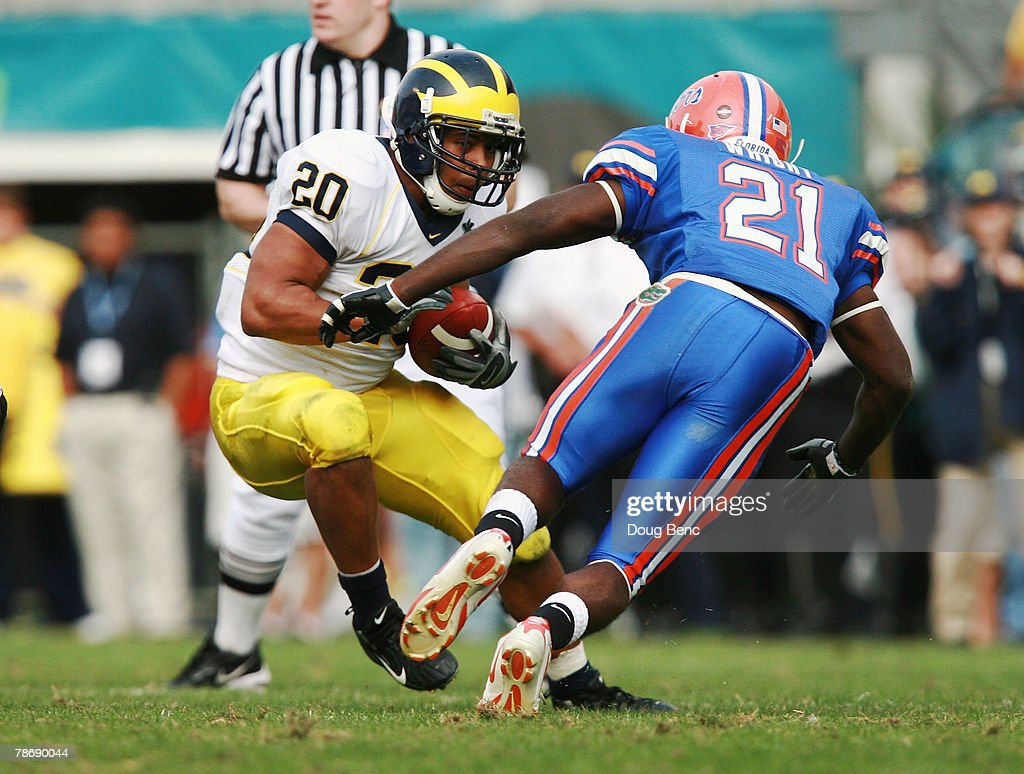 Running back Mike Hart of the Michigan Wolverines tries to avoid a tackle attempt by safety Major Wright the Florida Gators in the Capital One Bowl...