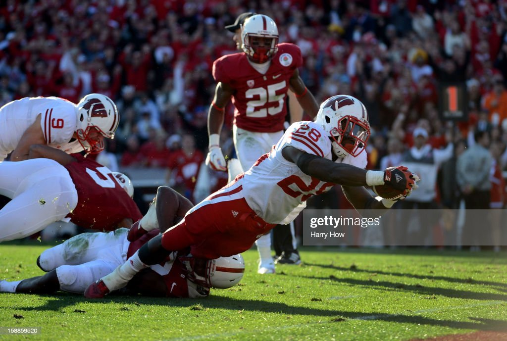 Running back <a gi-track='captionPersonalityLinkClicked' href=/galleries/search?phrase=Montee+Ball&family=editorial&specificpeople=6475135 ng-click='$event.stopPropagation()'>Montee Ball</a> #28 of the Wisconsin Badgers dives to score a 10-yard touchdown in the second quarter against the Stanford Cardinal in the 99th Rose Bowl Game Presented by Vizio on January 1, 2013 at the Rose Bowl in Pasadena, California.