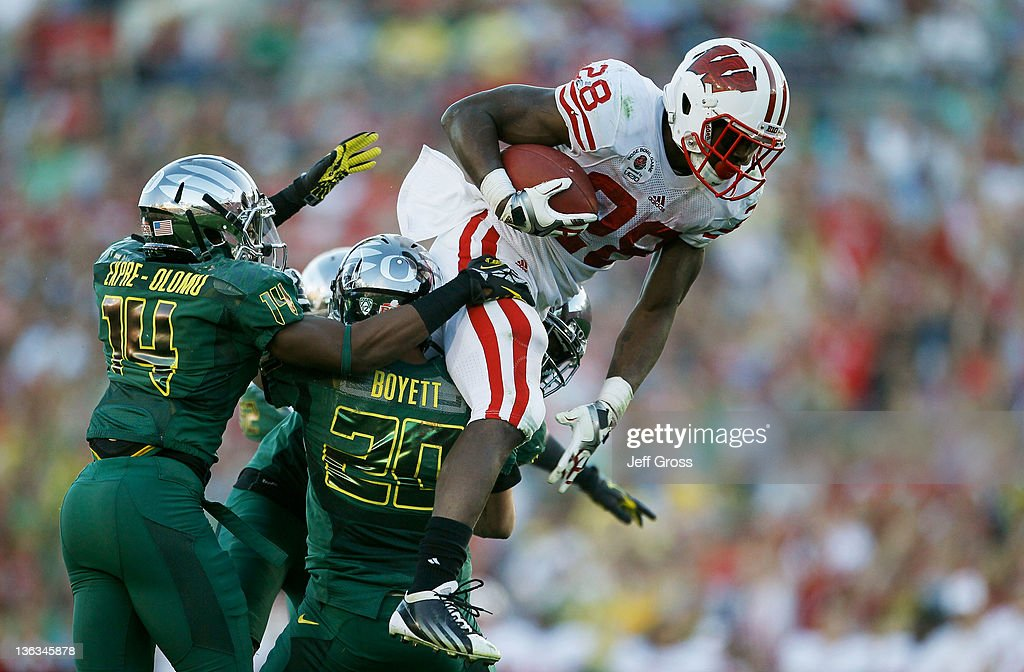 Running back Montee Ball #28 of the Wisconsin Badgers leaps over John Boyett #20 of the Oregon Ducks in the third quarter at the 98th Rose Bowl Game on January 2, 2012 in Pasadena, California.