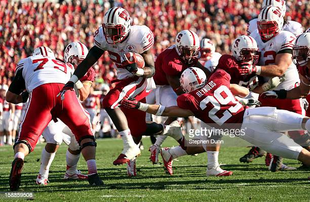 Running back Montee Ball of the Wisconsin Badgers scores a touchdown on a 10yard run in the first half against Ed Reynolds of the Stanford Cardinal...