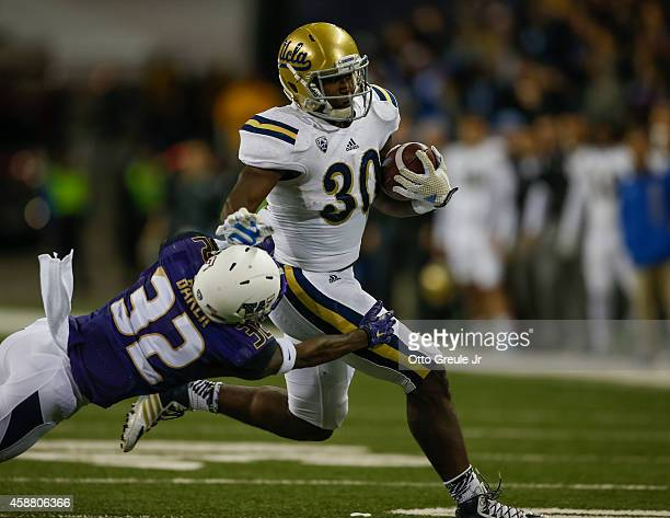 Running back Myles Jack of the UCLA Bruins rushes against Budda Baker of the Washington Huskies on November 8 2014 at Husky Stadium in Seattle...