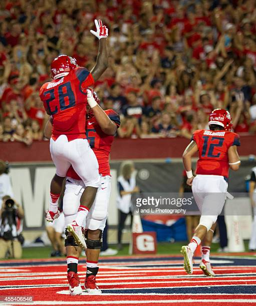 Running back Nick Wilson of the Arizona Wildcats celebrates his touchdown run with offensive linesman Steven Gurrola in a game against the Nevada...