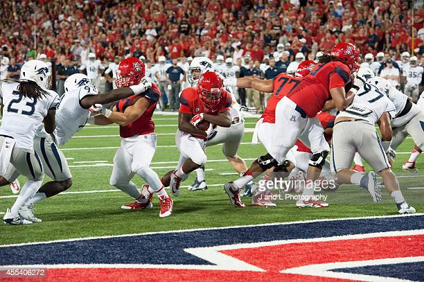 Running back Nick Wilson of the Arizona Wildcats rushes for a 2 yard touchdown in the first quarter against the Nevasa Wolf Pack at Arizona Stadium...