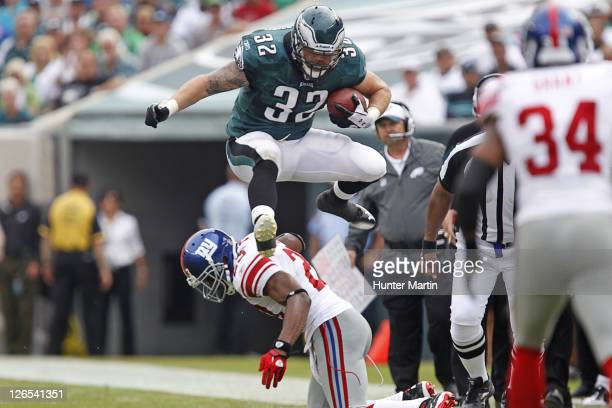 Running back Owen Schmitt of the Philadelphia Eagles hurdles cornerback Corey Webster of the New York Giants during a game on September 25 2011 at...