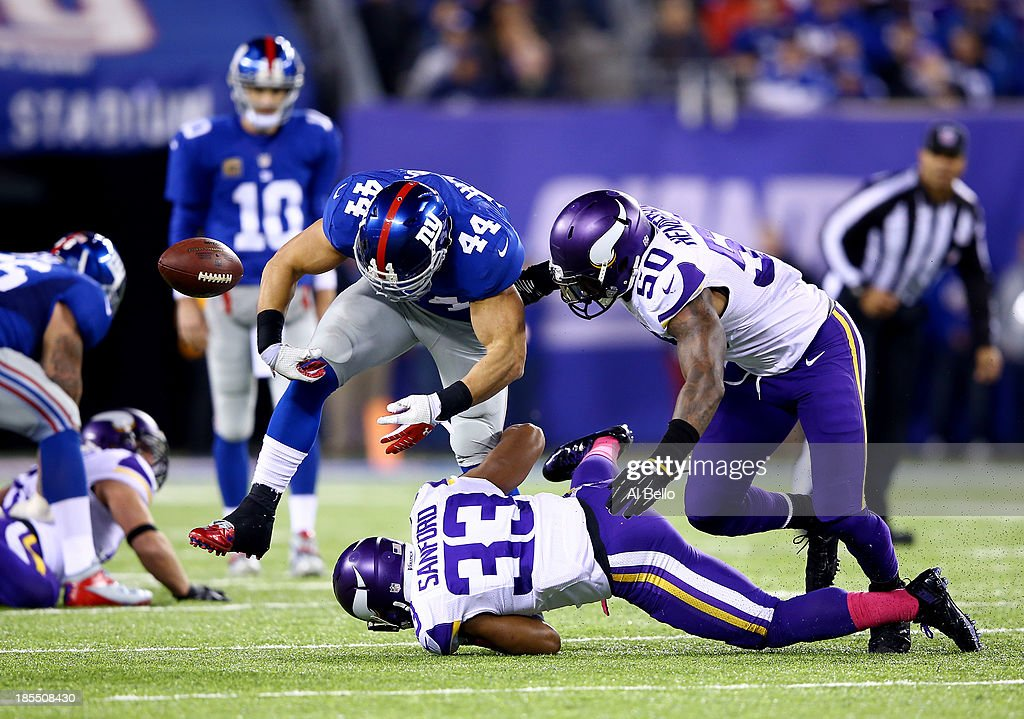 Running back Peyton Hillis #44 of the New York Giants loses the ball as strong safety Jamarca Sanford #33 and middle linebacker Erin Henderson #50 of the Minnesota Vikings make the tackle during a game at MetLife Stadium on October 21, 2013 in East Rutherford, New Jersey.