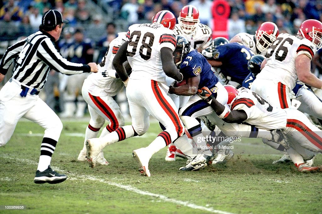 Running Back Priest Holmes #33 of the Baltimore Ravens gains a few yards before being tackled by Jamir Miller #95 and stopped by Defensive End Arnold Miller #98 both of the Cleveland Browns in a NFL game at PSINet Ravens Stadium on November 26 in Baltimore, Maryland. The Ravens won 44 to 7.
